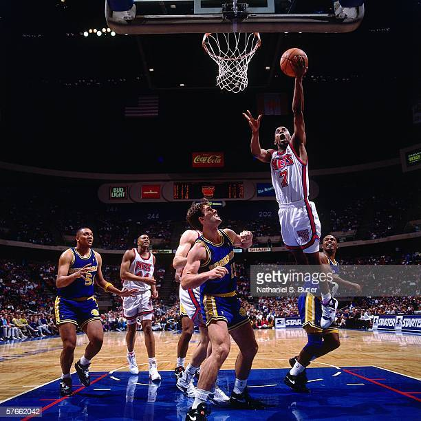 Kenny Anderson of the New Jersey Nets shoots a layup against Sarunas Marciulionis of the Golden State Warriors during a game circa 1991 at the...