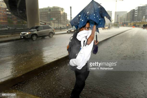 Kenny Anderson tries to keep his umbrella in his hands as the wind blows while trying to keep out of the pounding hail storm underneath the 20th...