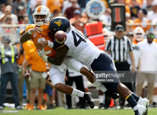 Kenny Bigelow Jr #40 of the West Virginia Mountaineers hits Jarrett Guarantano of the Tennessee Volunteers as he drops back to pass during their game...