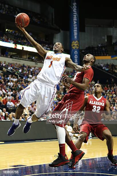 Kenny Boynton of the Florida Gators shoots against Devonta Pollard of the Alabama Crimson Tide in the second half during the semifinals of the SEC...