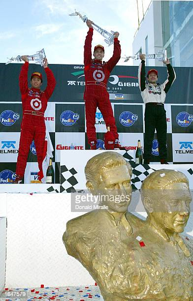 Kenny Brack celebrates winning with second placed Cristiano da Matta and third placed teammate Bruno Junqueira above the statue of Mexican racing...