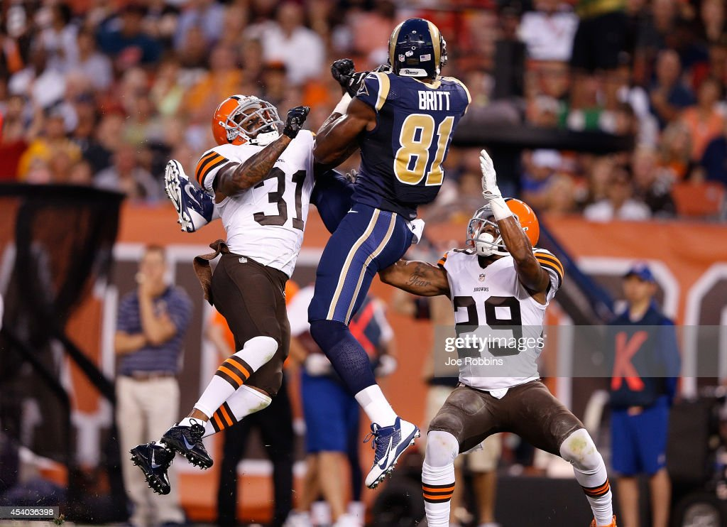 Kenny Britt #81 of the St. Louis Rams makes a catch between the defense of Donte Whitner #31 of the Cleveland Browns and Leon McFadden #29 of the Cleveland Browns during the first quarter at FirstEnergy Stadium on August 23, 2014 in Cleveland, Ohio.