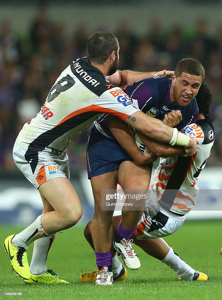 Kenny Bromwich of the Storm is tackled by Aaron Woods of the Tigers during the round 5 NRL match between the Melbourne Storm and the Wests Tigers at AAMI Stadium on April 8, 2013 in Adelaide, Australia.