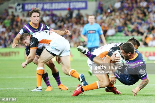 Kenny Bromwich of the Storm is tackled by Luke Brooks of the Tigers during the round two NRL match between the Melbourne Storm and the Wests Tigers...