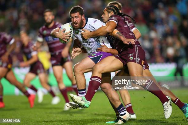 Kenny Bromwich of the Storm is tackled by Martin Taupau of the Sea Eagles during the round 18 NRL match between the Manly Sea Eagles and the...