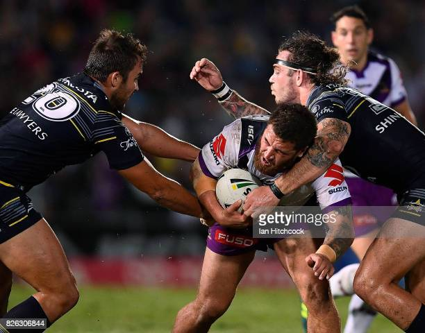 Kenny Bromwich of the Storm is tackled by Sam Hoare and Ethan Lowe of the Cowboys during the round 22 NRL match between the North Queensland Cowboys...
