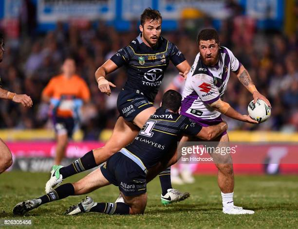 Kenny Bromwich of the Storm looks to pass the ball after making a break during the round 22 NRL match between the North Queensland Cowboys and the...