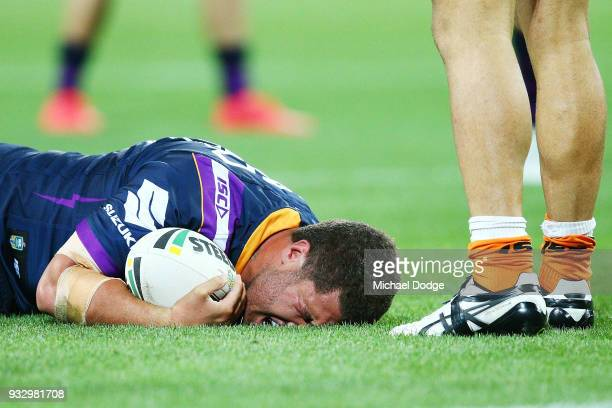 Kenny Bromwich of the Storm reacts in pain after being tackled by Luke Brooks of the Tigers during the round two NRL match between the Melbourne...