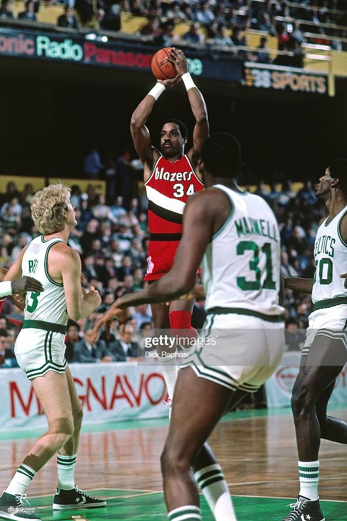 Kenny Carr #34 of the Portland Trail Blazers shoots a jumper over Larry Bird #33 and Cedric Maxwell #31 of the Boston Celtics during a game played in 1983 at the Boston Garden in Boston, Massachusetts.