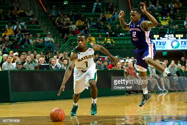 Kenny Chery of the Baylor Bears drives past Jalan West of the Northwestern State Demons on December 18 2013 at the Ferrell Center in Waco Texas