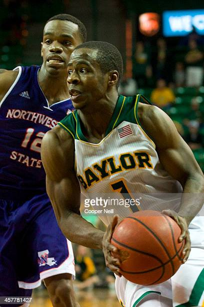 Kenny Chery of the Baylor Bears drives to the basket past Jalan West of the Northwestern State Demons on December 18 2013 at the Ferrell Center in...
