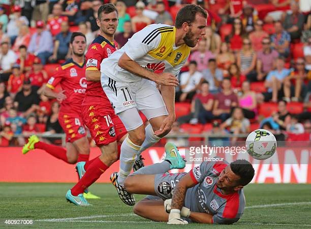 Kenny Cunningham of the Phoenix jumps over goalkeeper Paul Izzo of United as he makes a save during the round 14 ALeague match between Adelaide...