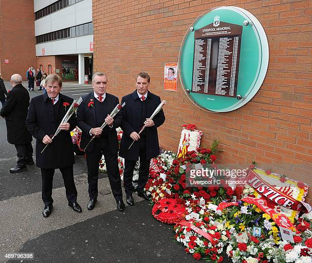 Kenny Dalglish former player and manager Ian Ayre managing director and Brendan Rodgers manager of Liverpool laying roses down before the memorial...