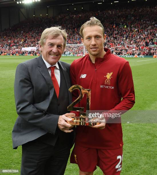 Kenny Dalglish former player and manager of Liverpool awards Lucas Leiva a trophy in recognition of ten years service during the Premier League match...