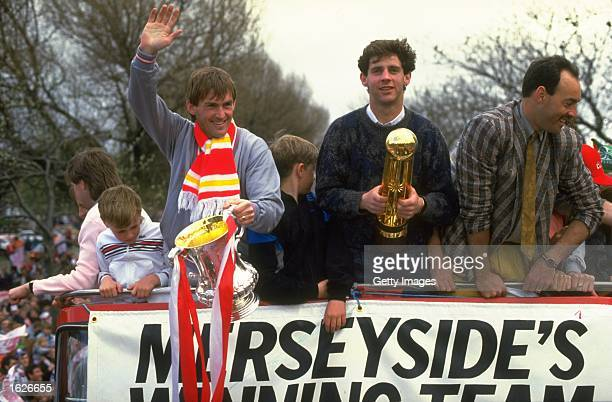 Kenny Dalglish Jim Beglin and Bruce Grobbelaar all of Liverpool stand on the top of their homecoming bus with the FA Cup and the Canon League...
