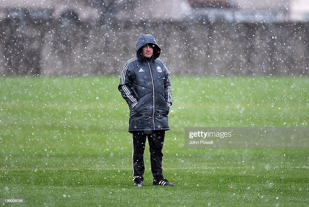 Kenny Dalglish manager of Liverpool stands in the snow as he conducts a Liverpool training session at Melwood Training Ground on December 16, 2011 in Liverpool, England.