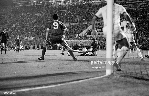 Kenny Dalglish of Liverpool is challenged by the AS Roma defence as he looks to score a goal as teammate Ian Rush looks on during the UEFA European...