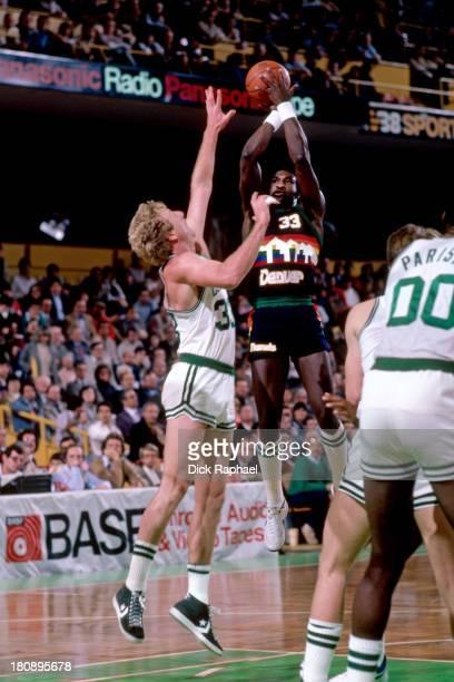 Kenny Denard of the Denver Nuggets shoots the ball over Larry Bird of the Boston Celtics during a game circa 1984 at the Boston Garden in Boston...