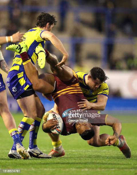 Kenny Edwards of Huddersfield Giants is tackled by Stefan Ratchford and Joe Philbin of Warrington Wolves during the Betfred Super League match...