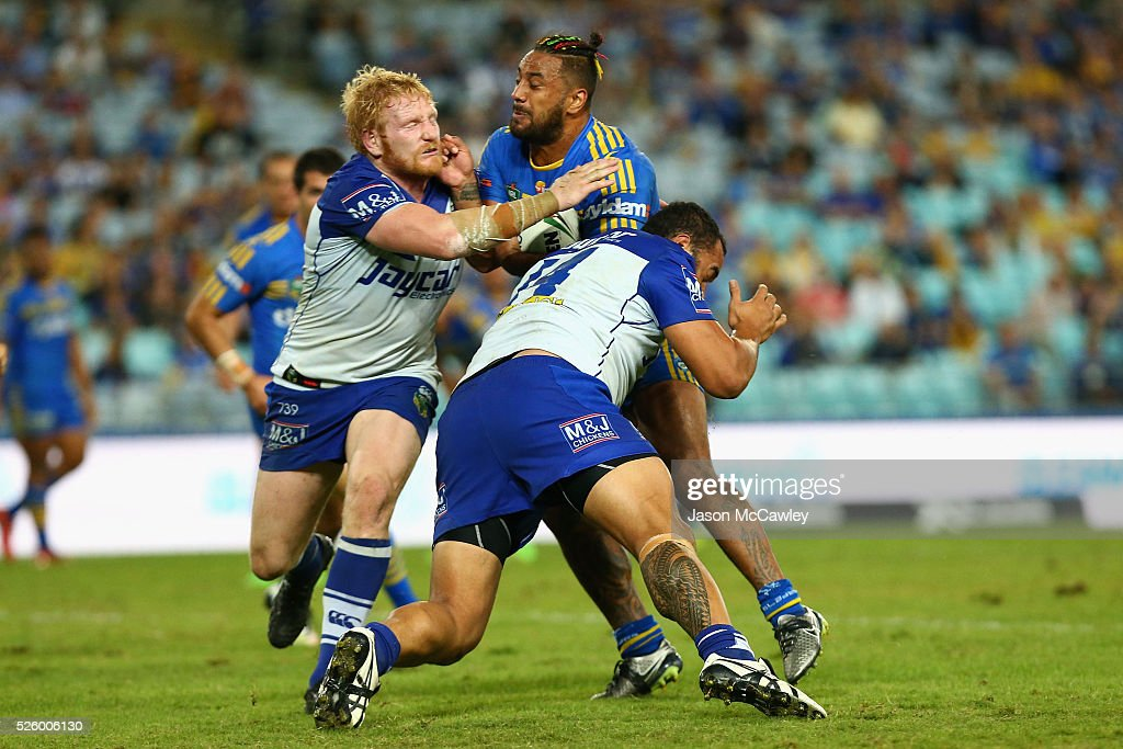 Kenny Edwards of the Eels is tackled by James Graham and Sam Kasiano of the Bulldogs during the round nine NRL match between the Parramatta Eels and the Canterbury Bulldogs at ANZ Stadium on April 29, 2016 in Sydney, Australia.