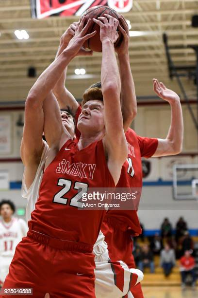 Kenny Foster of the Smoky Hill Buffaloes pulls a rebound away from Will Sass of the East High Angels during the first half of their class 5A round of...