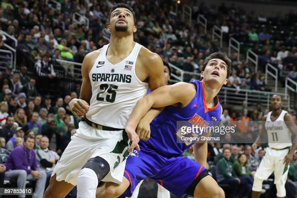 Kenny Goins of the Michigan State Spartans battles for a rebound with Oliver LynchDaniels of the Houston Baptist Huskies at the Jack T Breslin...