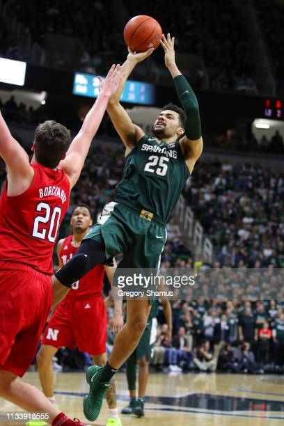 Kenny Goins of the Michigan State Spartans takes a first half shot over Tanner Borchardt of the Nebraska Cornhuskers at Breslin Center on March 05...