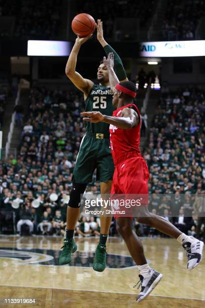 Kenny Goins of the Michigan State Spartans takes a first half shot next to Glynn Watson Jr #5 of the Nebraska Cornhuskers during the first half at...