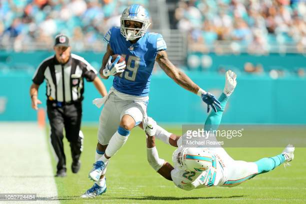 Kenny Golladay of the Detroit Lions breaks a tackle from TJ McDonald of the Miami Dolphins during the second half at Hard Rock Stadium on October 21...