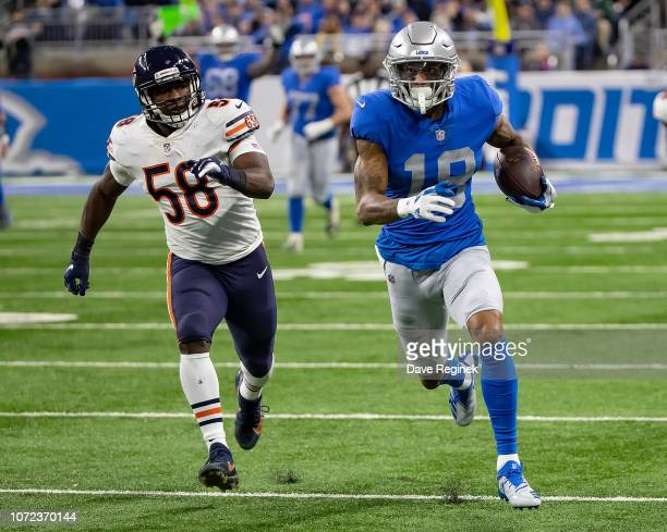 Kenny Golladay of the Detroit Lions runs with the football in front of Roquan Smith of the Chicago Bears during an NFL Thanksgiving Day game at Ford...