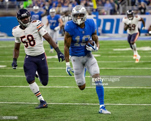 Kenny Golladay of the Detroit Lions runs with the football in front of Roquan Smith of the Chicago Bears during an NFL, Thanksgiving Day game at Ford...