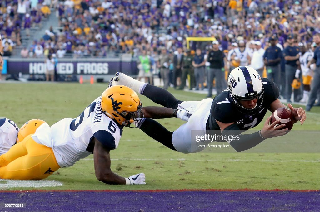 Kenny Hill #7 of the TCU Horned Frogs dives into the end zone to score the game winning touchdown against Dravon Askew-Henry #6 of the West Virginia Mountaineers in the fourth quarter at Amon G. Carter Stadium on October 7, 2017 in Fort Worth, Texas. The TCU Horned Frogs beat the West Virginia Mountaineers 31-24.