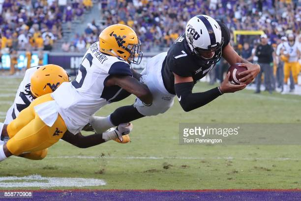 Kenny Hill of the TCU Horned Frogs dives into the end zone to score the game winning touchdown against Dravon AskewHenry of the West Virginia...
