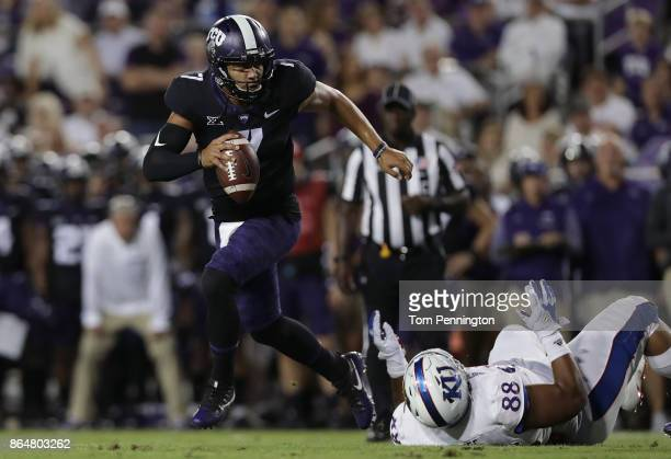 Kenny Hill of the TCU Horned Frogs rolls out and throws a touchdown pass against JJ Holmes of the Kansas Jayhawks in the first quarter at Amon G...