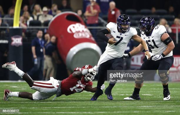 Kenny Hill of the TCU Horned Frogs tries to get away from Emmanuel Beal of the Oklahoma Sooners as Austin Schlottmann of the TCU Horned Frogs looks...