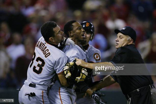 Kenny Lofton of the San Francisco Giants is held by teammates Rich Aurilia and Benito Santiago after Lofton was brushed back by a pitch during game 1...
