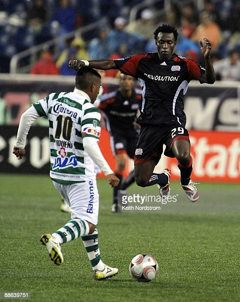 Kenny Mansally of the New England Revolution jumps to block a shot by Daniel Luduena of Santos Laguna during Super Liga Group B match on June 21,...