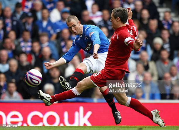 Kenny Miller of Rangers kicks the ball past Scott Severin of Aberdeen during the Scottish Premier League match between Rangers and Aberdeen at Ibrox...