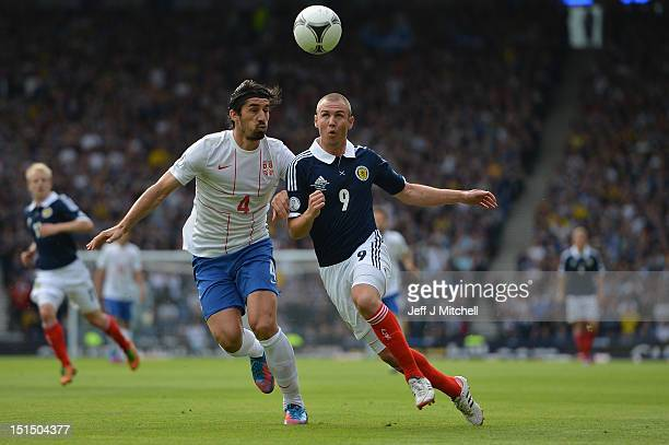 Kenny Miller of Scotland tackles Milan Bisevac of Serbia during the FIFA 2014 World Cup Qualifier at Hampden Park between Scotland and Serbia on...