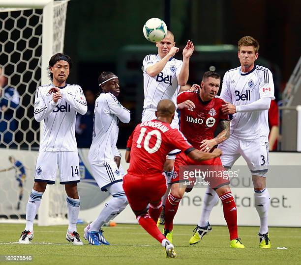 Kenny Miller of the Vancouver Whitecaps FC leaps to play a free kick by Robert Earnshaw of the Toronto FC during their MLS game at BC Place March 2...