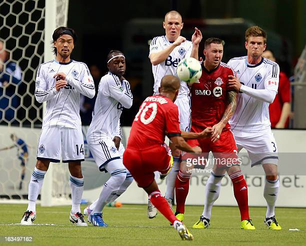 Kenny Miller of the Vancouver Whitecaps FC leaps to play a free kick by Robert Earnshaw of the Toronto FC during their MLS game March 2 2013 in...