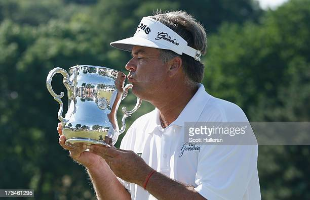Kenny Perry kisses the trophy after his fivestroke victory at the 2013 US Senior Open Championship at Omaha Country Club on July 14 2013 in Omaha...