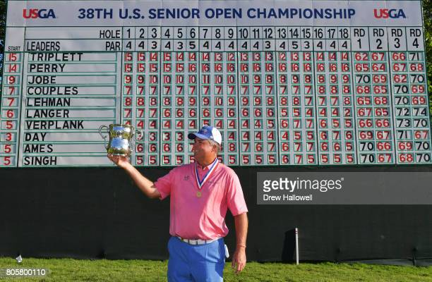 Kenny Perry stands in front of the final leaderboard while holding the Francis D Ouimet Memorial Trophy after winning 2017 US Senior Open...