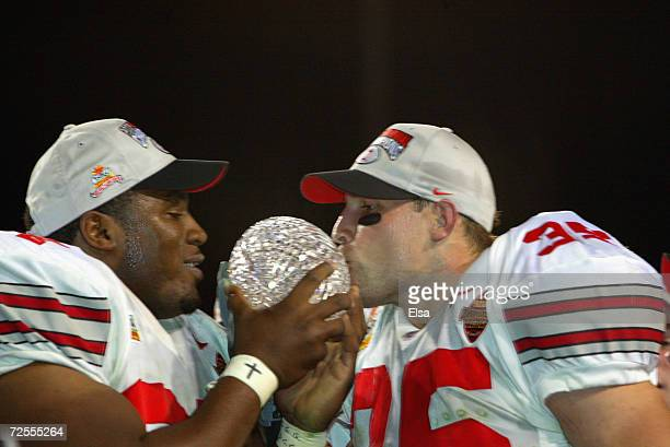 Kenny Peterson and Matt Wilheim of the Ohio State Buckeyes celebrate with the National Championship trophy after defeating the Miami Hurricanes 3124...