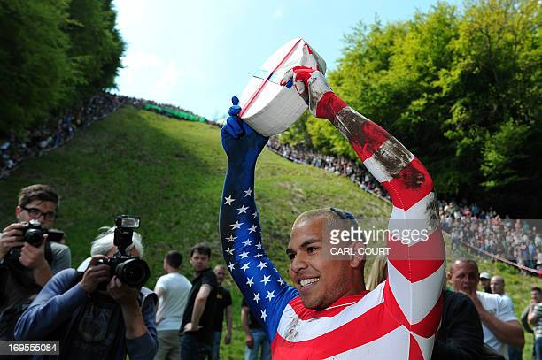 Kenny Rackers from the US celebrates winning the first race down Coopers Hill in pursuit of a fake foam round Double Gloucester cheese during the...
