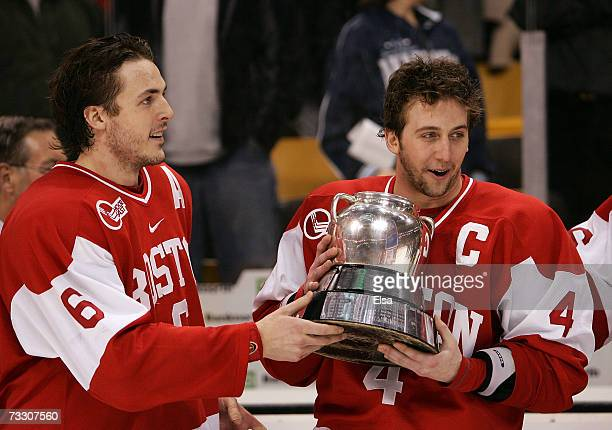 Kenny Roche and Sean Sullivan of the Boston University Terriers take the Beanpot trophy after their overtime win over the Boston College Eagles...