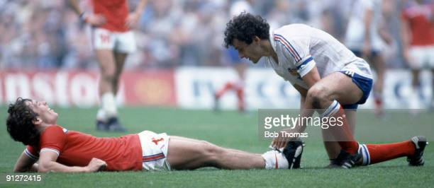 Kenny Sansom of England is helped while injured by Michel Platini of France during the England v France World Cup match played in Bilbao, Spain on...