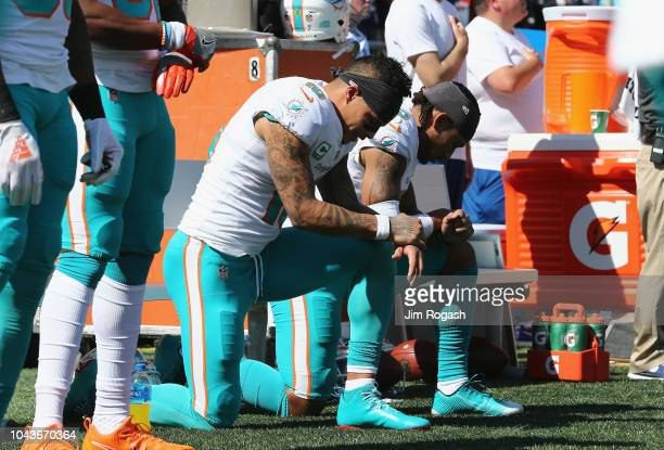 Kenny Stills and Albert Wilson of the Miami Dolphins kneel during the national anthem prior to their game against the New England Patriots at...