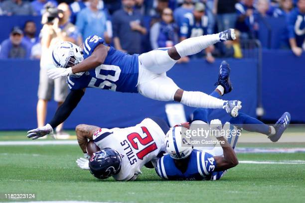 Kenny Stills of the Houston Texans catches a pass while being tackled by Anthony Walker and Rock Ya-Sin of the Indianapolis Colts during the third...