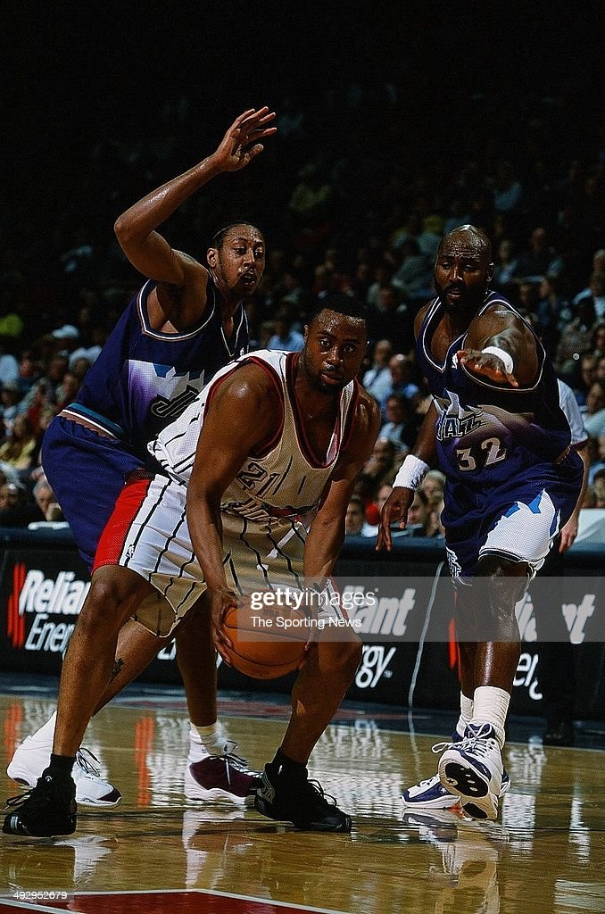 Kenny Thomas #21 of the Houston Rockets moves past Donyell Marshall #42 and Karl Malone #32 of the Utah Jazz during the game on March 27, 2001 at the Compaq Center in Houston, Texas. The Rockets won 109-86.